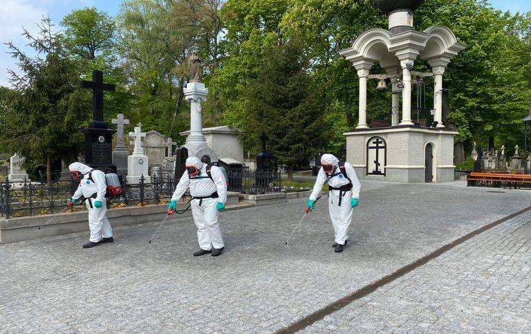 Mężczyźni dezynfekujący chodnik