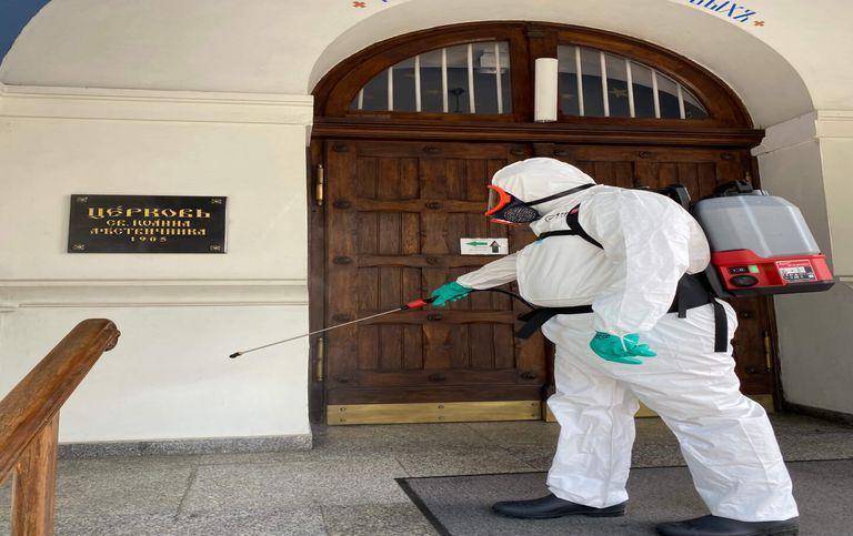 Mężczyzna dezynfekujący drzwi
